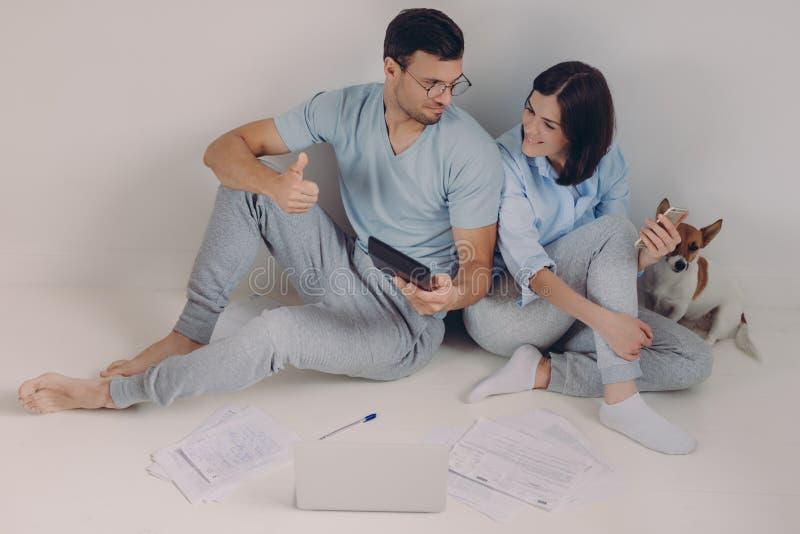 De foto van de tevreden mens draagt bril en de vrijetijdskleding, toont o.k. cijfer op calculator, demonstartes gebaar, verheugt  stock foto's