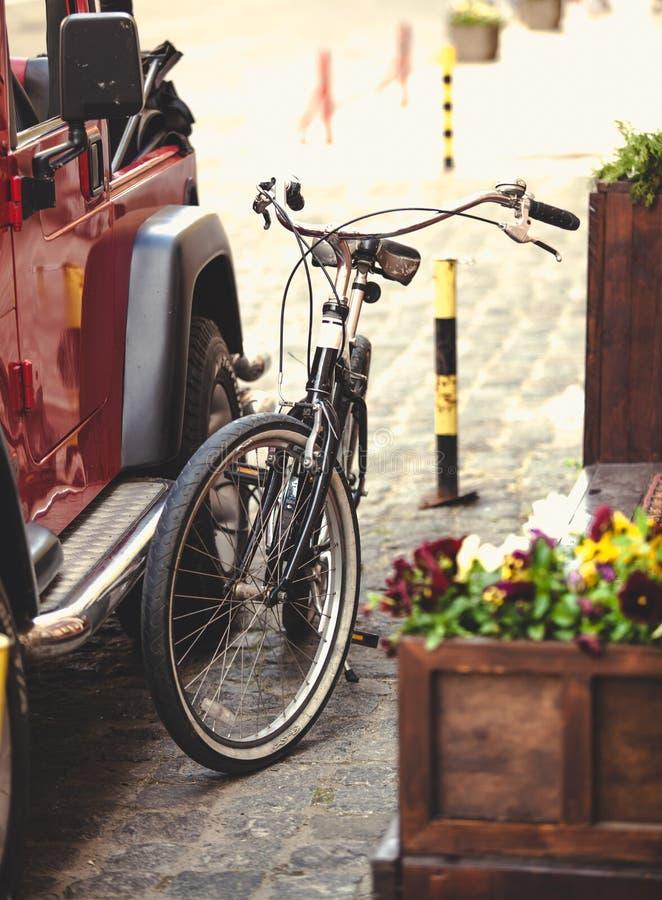 De foto van uitstekende fiets hitched aan auto met ketting stock fotografie