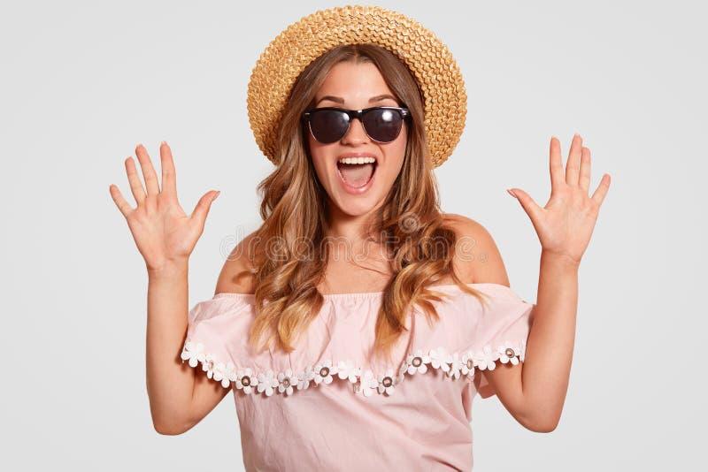 De foto van verbaasde aantrekkelijke vrouw met extatische uitdrukking, reageert op prachtig iets, houdt handen opgeheven, uitroep stock foto's