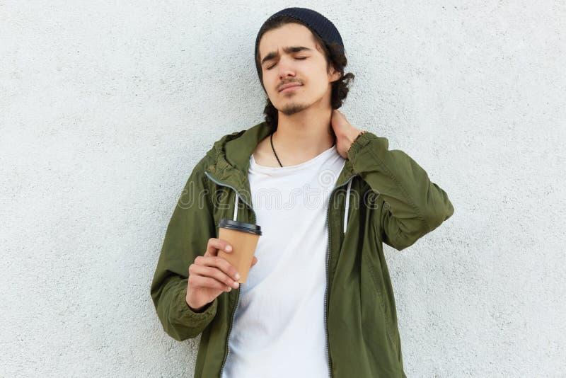 De foto van de vermoeide krullende mens houdt hand op hals, gekleed in modieuze kleren, houdt aromatische koffie of cappucino, vo royalty-vrije stock fotografie