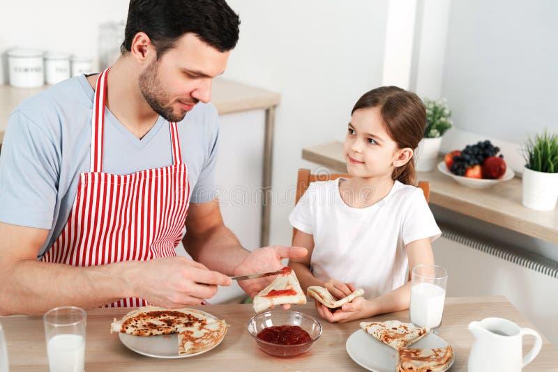 De foto van vriendschappelijke familie heeft samen ontbijt De gebaarde mens spreidt jam op dunne gebraden pannekoek uit, zit met  stock foto's