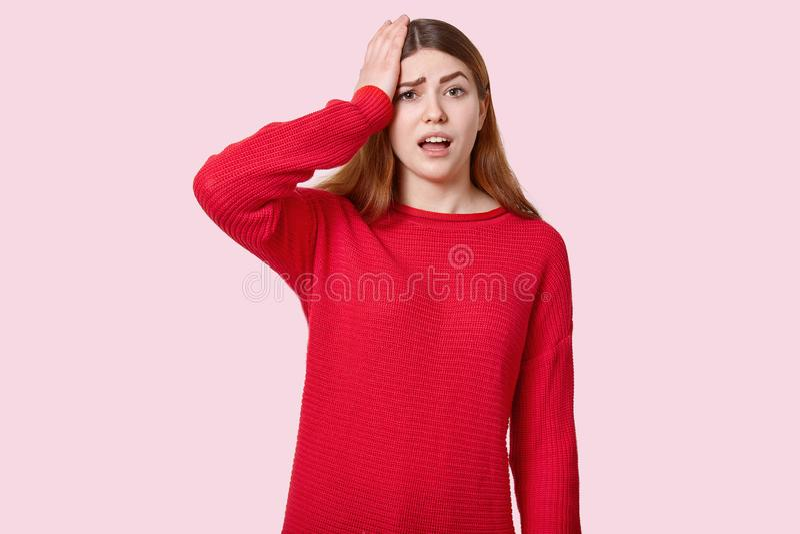 De foto van wanhopige jonge Europese vrouw houdt hand op hoofd, betreurt iets, heeft in verwarring gebracht gelaatsuitdrukking, g stock fotografie