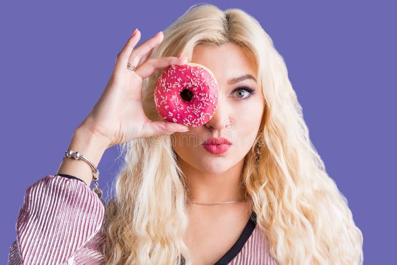 De foto van wijfje houdt zoete heerlijke doughnut royalty-vrije stock afbeeldingen