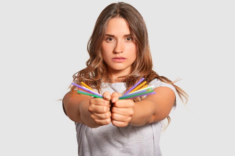 De foto van zelf verzekerde vrouwelijke modellen draagt plastic kleurrijk stro in beide handen, bekijkt direct camera, die againt stock fotografie