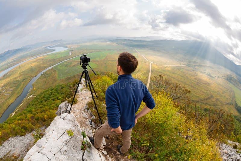 De fotograaf bovenop de berg neemt de camera over stock afbeelding