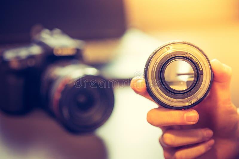 De fotograaf houdt een fotografielens in zijn hand, camera en laptop op de onscherpe achtergrond stock foto