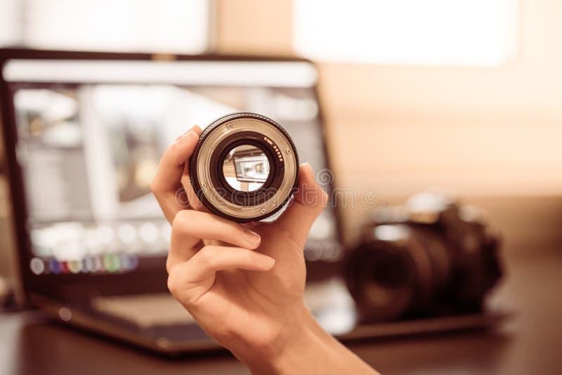 De fotograaf houdt een fotografielens in zijn hand, camera en laptop op de onscherpe achtergrond stock fotografie