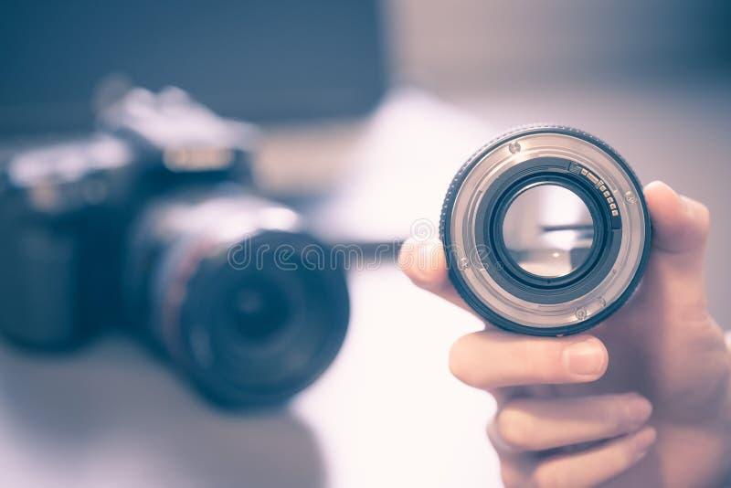De fotograaf houdt een fotografielens in zijn hand, camera en laptop op de onscherpe achtergrond royalty-vrije stock foto