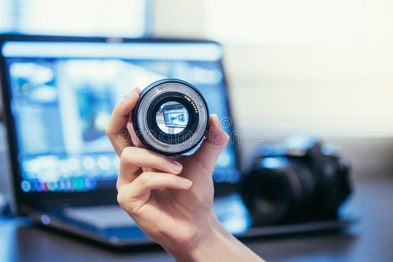 De fotograaf houdt een fotografielens in zijn hand, camera en laptop op de onscherpe achtergrond royalty-vrije stock foto's