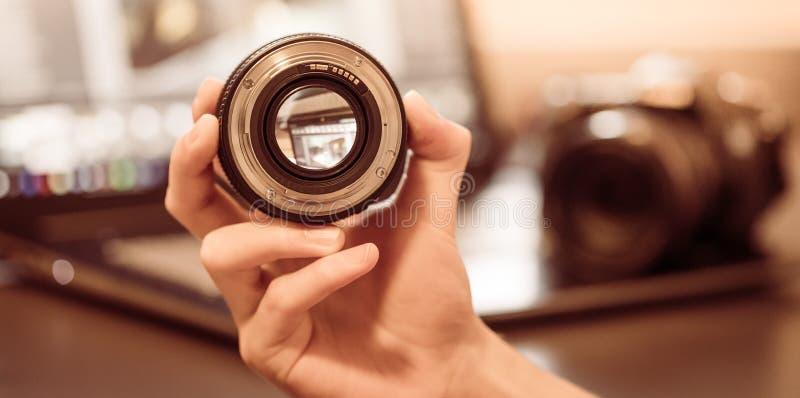 De fotograaf houdt een fotografielens in zijn hand, camera en laptop op de onscherpe achtergrond stock foto's