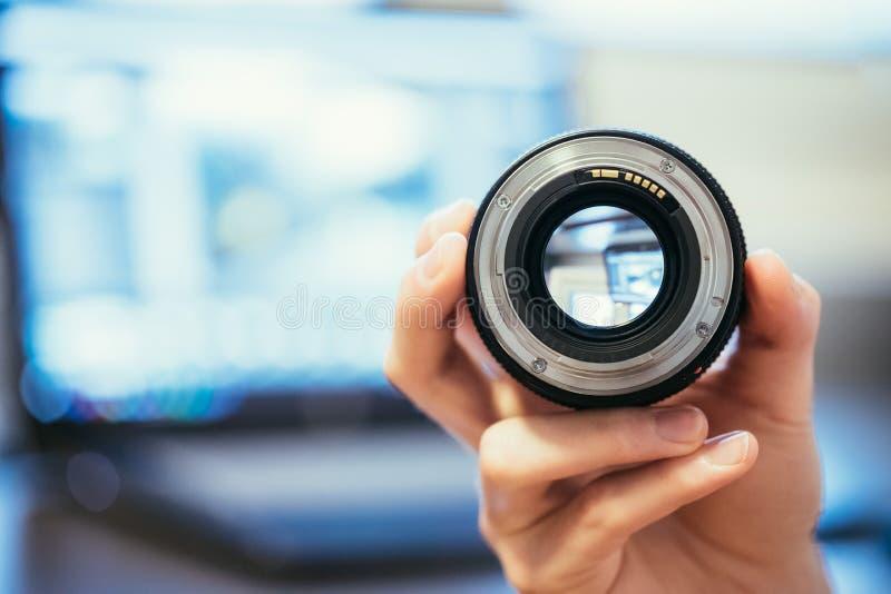 De fotograaf houdt een fotografielens in zijn hand, laptop op de onscherpe achtergrond stock fotografie