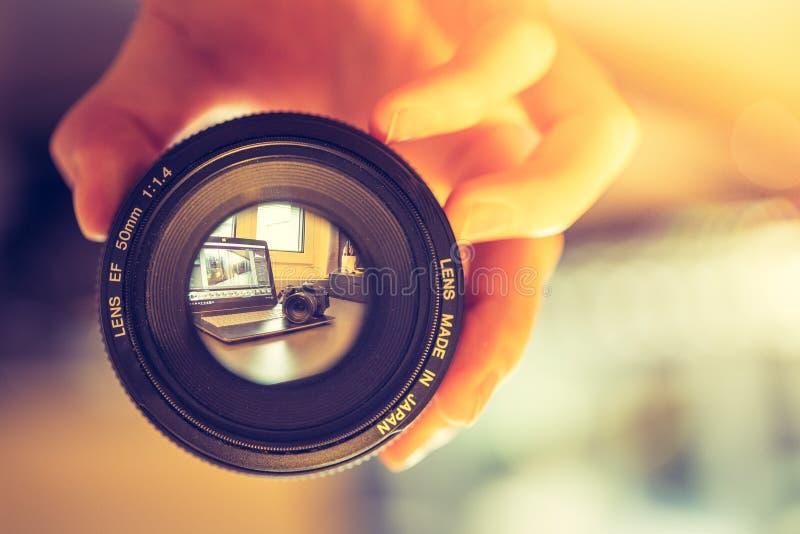 De fotograaf houdt een fotografielens in zijn hand, laptop op de onscherpe achtergrond stock foto