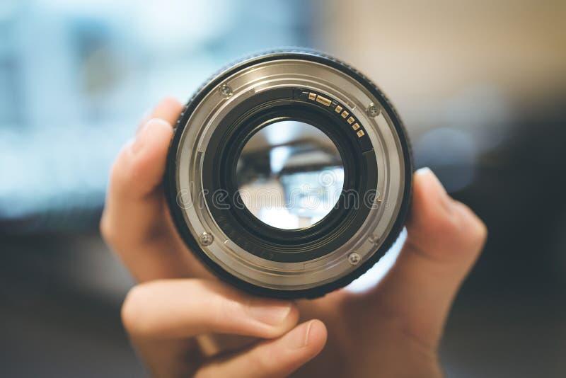 De fotograaf houdt een fotografielens in zijn hand, laptop op de onscherpe achtergrond stock foto's