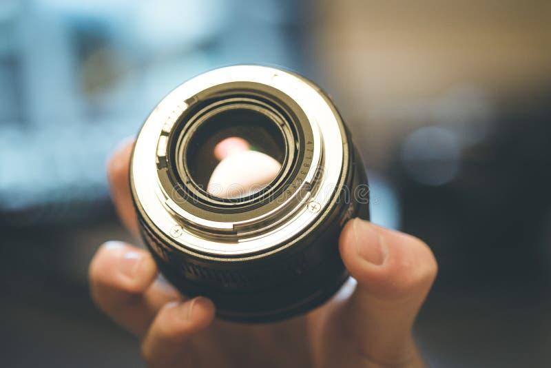 De fotograaf houdt een fotografielens in zijn hand, laptop op de onscherpe achtergrond stock afbeeldingen