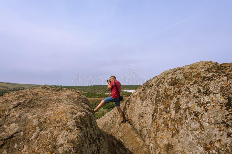 De fotograaf neemt beelden van aard, die zich bovenop een klip bevinden royalty-vrije stock fotografie