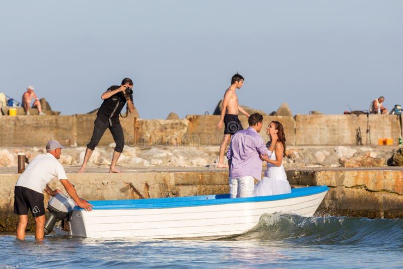 De fotograaf schiet een paar hartelijke jonggehuwden in een boot in de baai van de Zwarte Zee royalty-vrije stock foto's