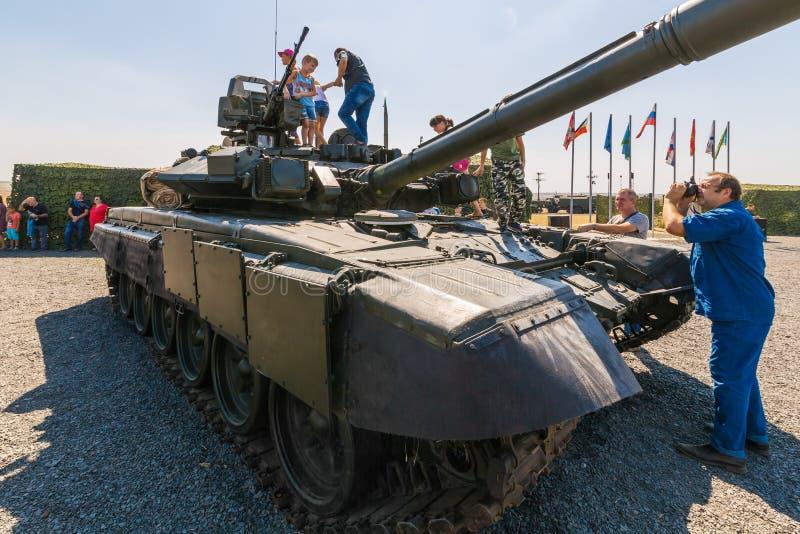 De fotograaf schiet jonge bezoekers van de tentoonstelling op de tank t-90A royalty-vrije stock foto's