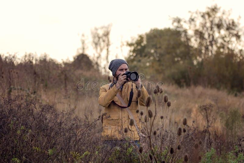 De Fotograaf van de aard Mens in het gras die van het moerasland foto nemen bij avond royalty-vrije stock foto
