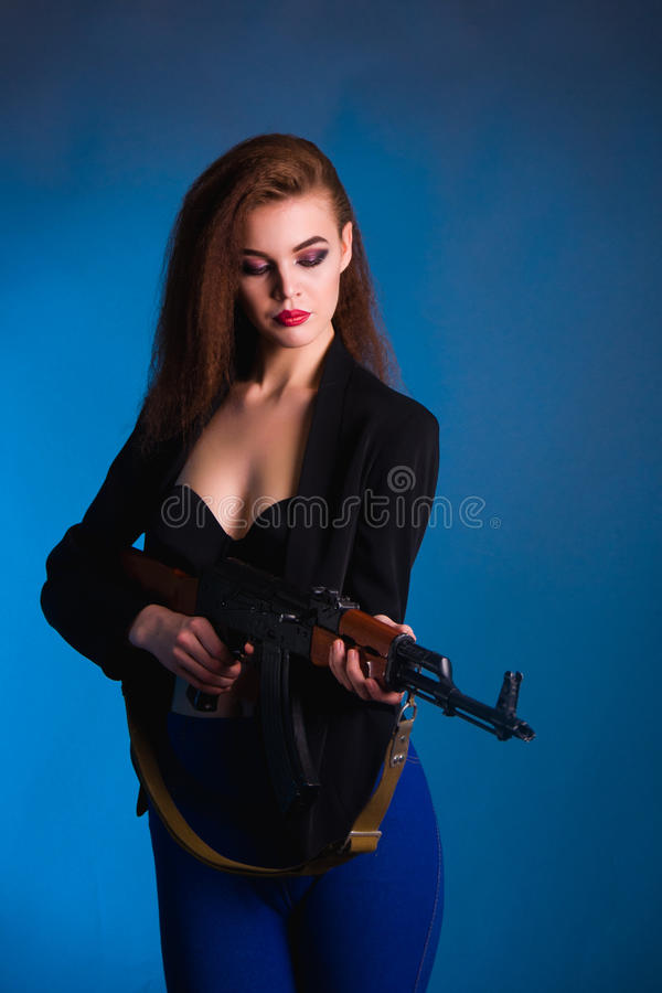 De fotografie van de meisjesmanier in de studio met een kanon is gevaarlijk stock afbeeldingen