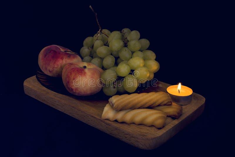 De fotografie van het voedselstilleven met hoogten, druiven en kaarslicht stock foto's