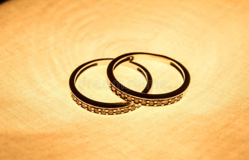 De fotografie van juwelen Drie gouden ringen op gradiënt weerspiegelende oppervlakte Achtergrond stock afbeelding