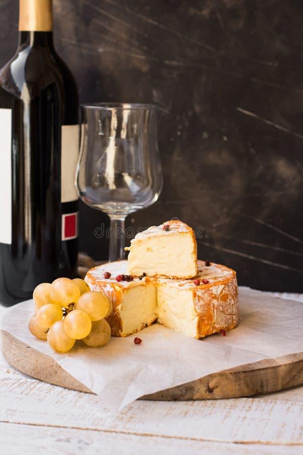 De Franse kaas van Munster met oranje schil, Spaanse peperkorrels, witte druiven sneed plak, wijnfles en glas af royalty-vrije stock foto's