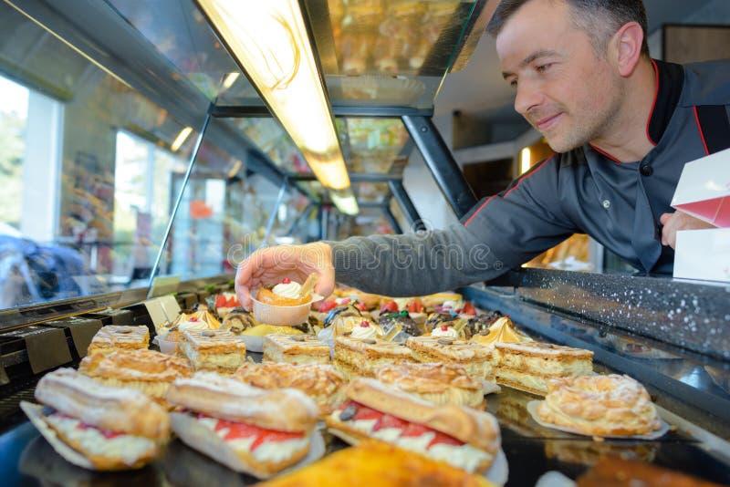 De Franse patisseriechef-kok plaatst desserts in vertoningsteller royalty-vrije stock fotografie