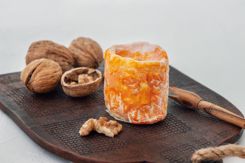 De Franse zachte kaas van Epoisses met witte vorm met een mooie sinaasappelschil op een bruine plaat Sluit omhoog royalty-vrije stock foto