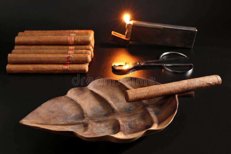 DE FRESHEST HAND MAAKTE CUBAN CIGARS MET EEN WOODEN ASHTRAS EEN CIGAR CUTTER EN EEN LICHTER stock afbeelding