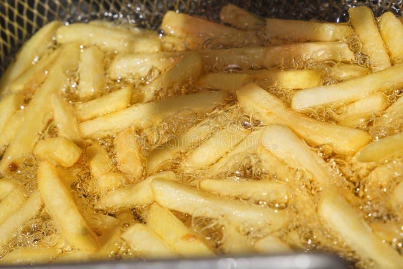 De frieten worden voorbereid in hete olie in een speciaal metaalnet stock foto's