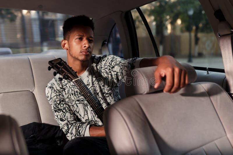 De fronsende mens die in auto een gitaar, gezet in achterbank van auto houden, zette zijn hand op de bestuurderszitplaats Licht o stock afbeelding
