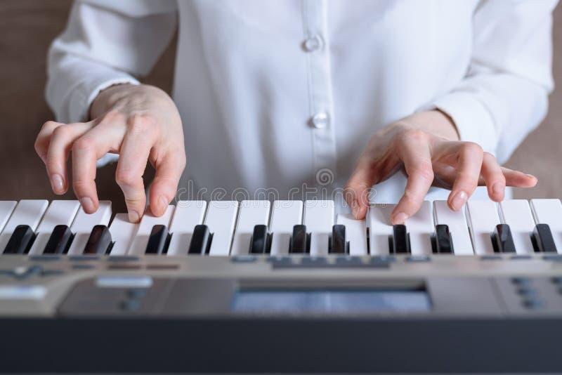 De frontale mening van vrouwelijke handen praktizeerde speel de synthesizer stock afbeeldingen
