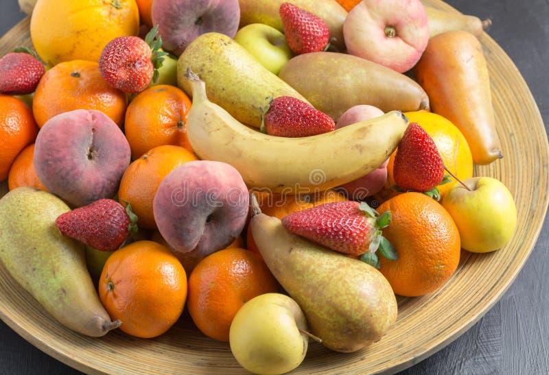 De fruitkom met exotische gehele vruchten sluit omhoog in rustiek houten BO stock afbeeldingen