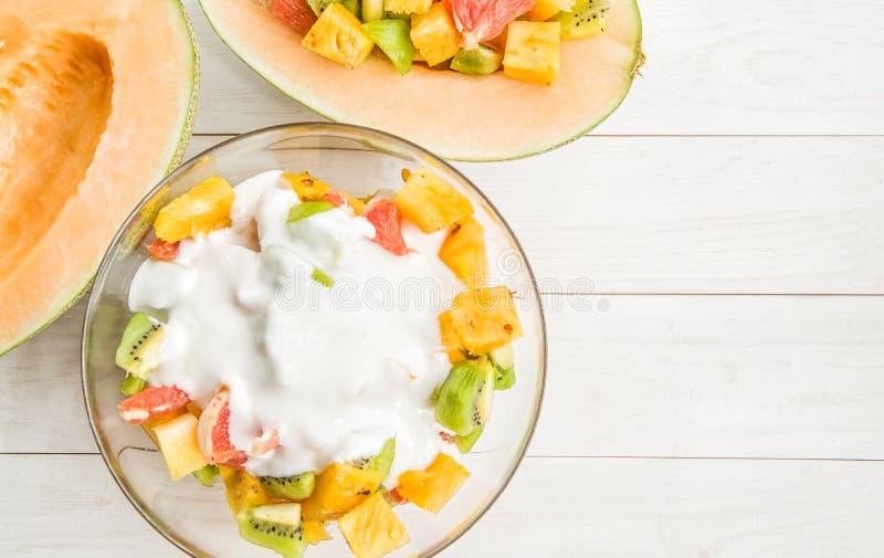 De fruitsalade in een kom met yoghurt en de twee helften ofmelon op witte houten vlakte als achtergrond leggen hoogste mening royalty-vrije stock fotografie