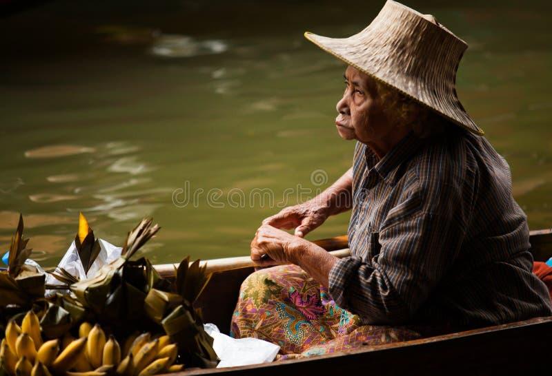 De fruittuinman, koopvaardijhandelaar roeit boot om opbrengst aan toeristen bij het Drijven van Damnoen te verkopen Saduak Markt, stock afbeelding