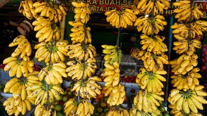 De fruitwinkels in traditionele markten in Indonesië verkopen bananen die keurig worden geschikt en voor de winkel getoond stock fotografie