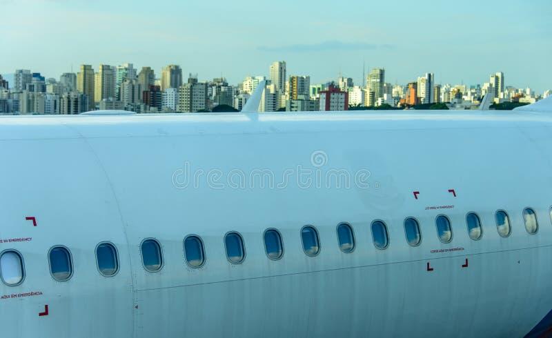 De fuselage van de smal-lichaamsvliegtuigen met witte wolken en blauwe hemel dacht in de patrijspoorten na stock foto's