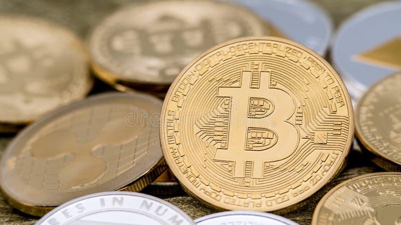 De fysieke munt die van metaal gouden Bitcoin over anderen muntstukken roteren btc stock afbeeldingen