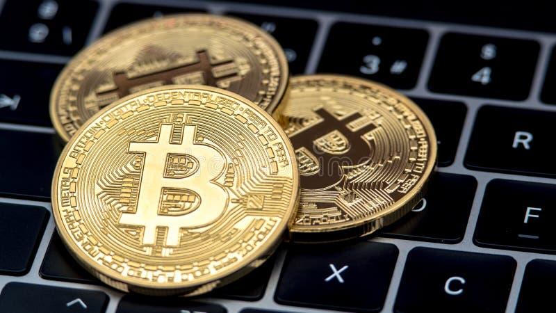 De fysieke munt van metaal gouden Bitcoin op het toetsenbord van de notitieboekjecomputer btc stock foto
