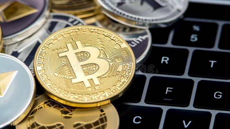 De fysieke munt van metaal gouden Bitcoin op het toetsenbord van de notitieboekjecomputer btc stock foto's