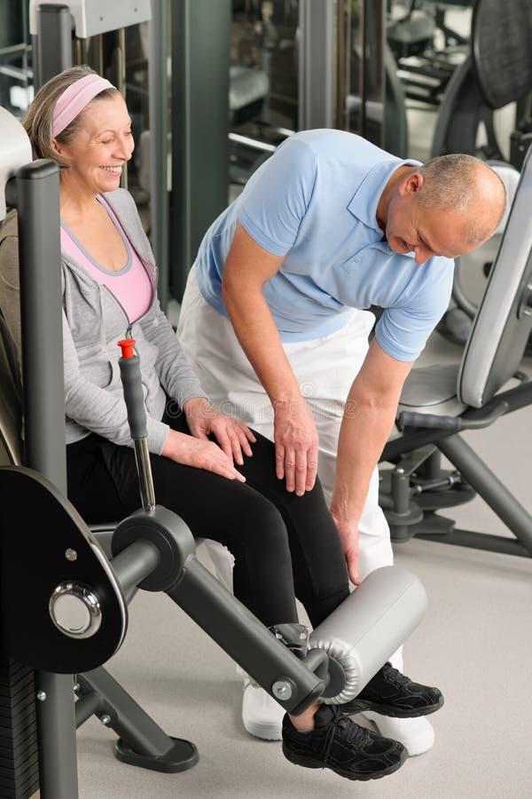 De fysiotherapeut staat actieve hogere vrouw gymnastiek bij royalty-vrije stock fotografie