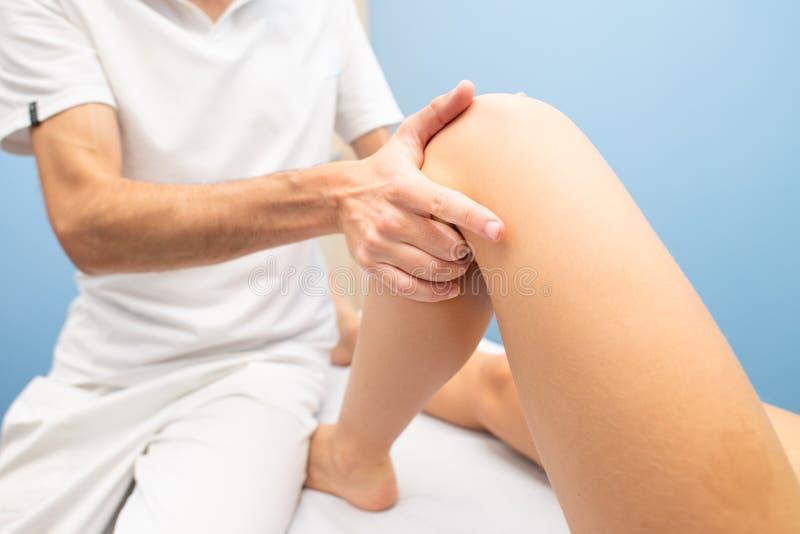 De fysiotherapeut voert de test van de knielade aan een vrouw uit stock foto