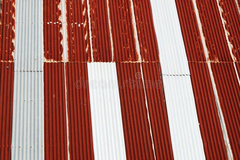 De gamla galvaniserade taken, som var tunna, rostat, var röda och att växla med grå färger royaltyfria bilder