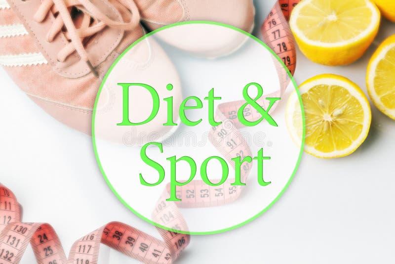 De gamla gymnastikskorna, ett meterband och citron på en vit arkivfoton