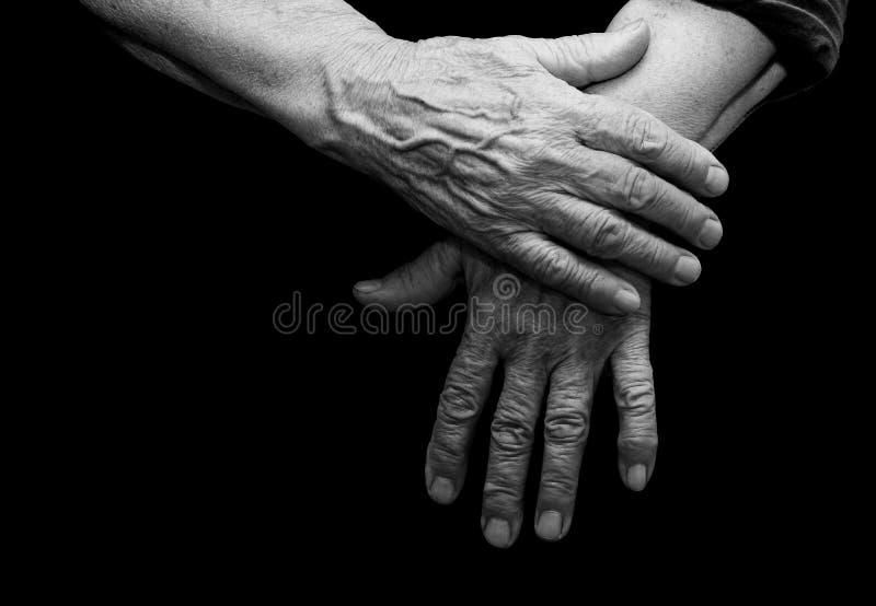 De gamla händerna på en svart bakgrund royaltyfri fotografi