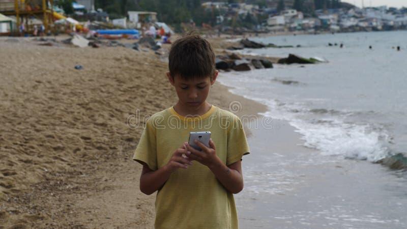 De gang van de reizigersjongen op het strand en het gebruiken van smartphone in de avond, praatjes, schrijft sms Het gebruiken va stock fotografie