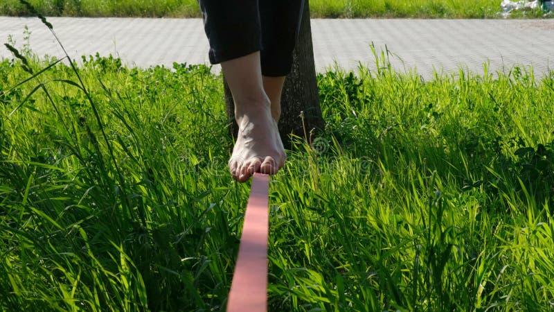 De gang van vrouwenbenen volgens een strakke lijn in het park De saldi van de voetvrouw op slackline sluiten omhoog royalty-vrije stock foto's