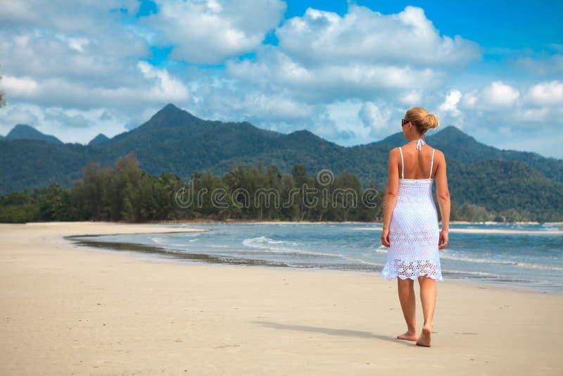 De gangen van de vrouw op een strand royalty-vrije stock afbeelding