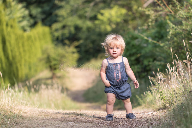 De gangen van het babymeisje op groene bosweg royalty-vrije stock foto