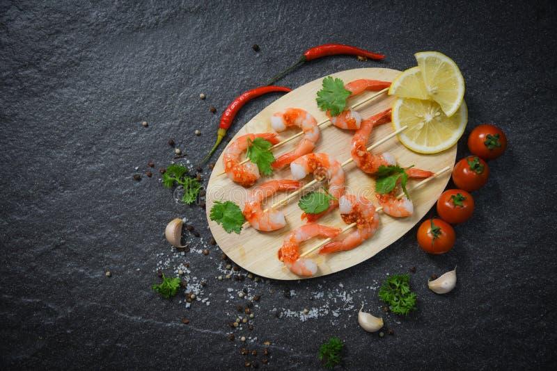 De garnalengarnalen doorsteekt zeevruchten die met sauskruiden en kruiden worden gekookt op houten achtergrond - sluit gekookte s royalty-vrije stock foto